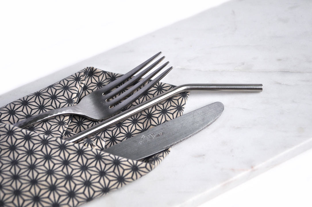 Image of Silverware, a patterned napkin and a marble cheese board