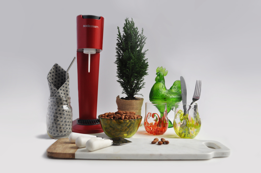 Image of items that can be used for zero waste entertaining: a soda stream, a cloth napkin, silverware, glasses, plants, marble cutting board