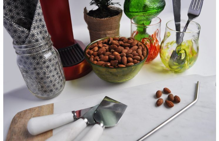 Image of a marble and wood cheese board, a stainless steele reusable straw, a bowl of almonds, silverware, handblown glasses, and a cloth napkin