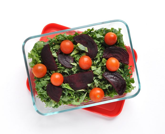 Image of a rectangular Pyrex dish filled with green kale, purple beets, and red cherry tomatoes