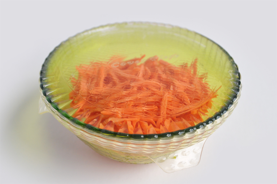 Image of a green bowl filled with orange carrots, covered in a clear silicone stretchable lid
