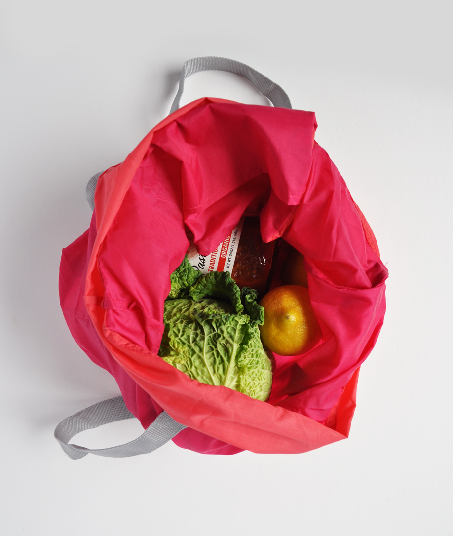 Image of a coral colored flip & tumble reusable bag with a cabbage, a lemon and a jar inside
