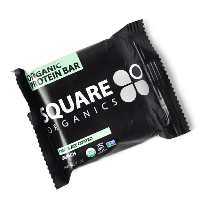 Image of a square protein bar in a black wrapper, an item that is typically not recyclable