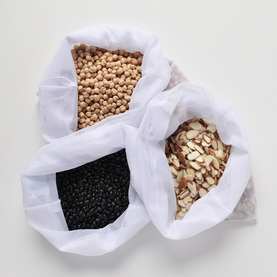 Image of three flip & tumble reusable produce bags, filled with chick peas, black beans, and sliced almonds