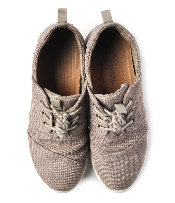 Image of a pair of tan TOMS shoes on a white background