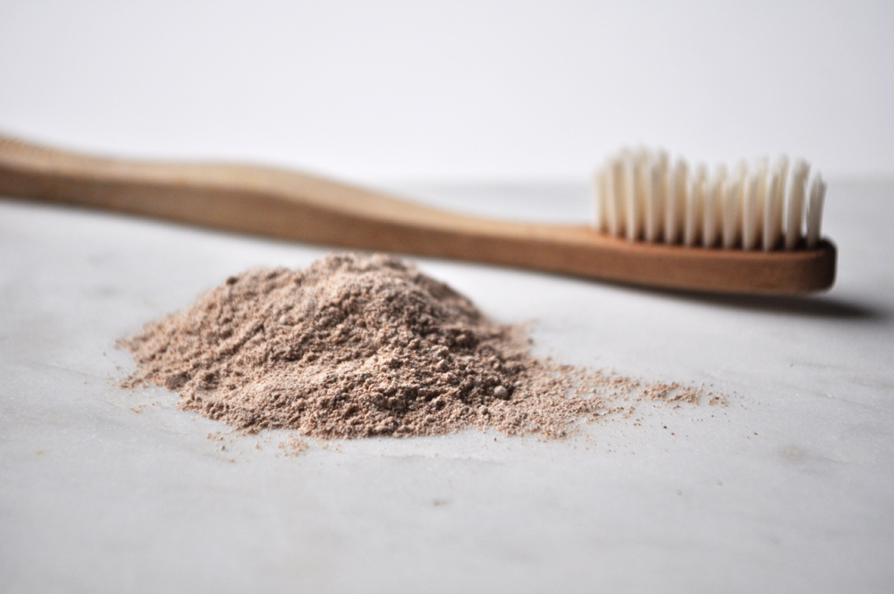 Image of a bamboo toothbrush lying next to homemade tooth powder