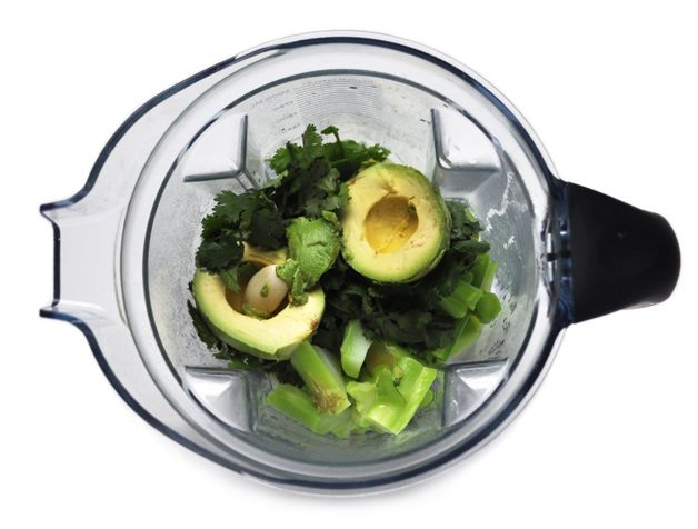 Image of a blender with avocados, broccoli, cilantro and garlic in it