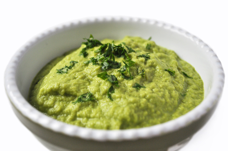 Image of a bowl with lime green colored salsa verde in it, topped with finely chopped cilantro on a white background