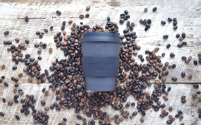 Image of a black ecoffee cup resting on top of coffee beans on a wooden surface