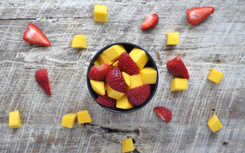 Image of an ecoffee cup filled with mangoes and strawberries on a wooden surface