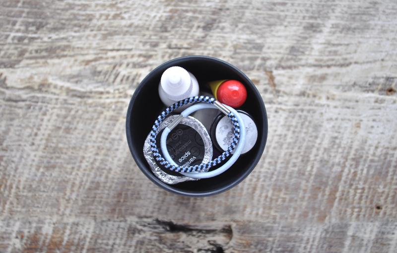 Image of an ecoffee cup filled with toiletries on a wooden surface