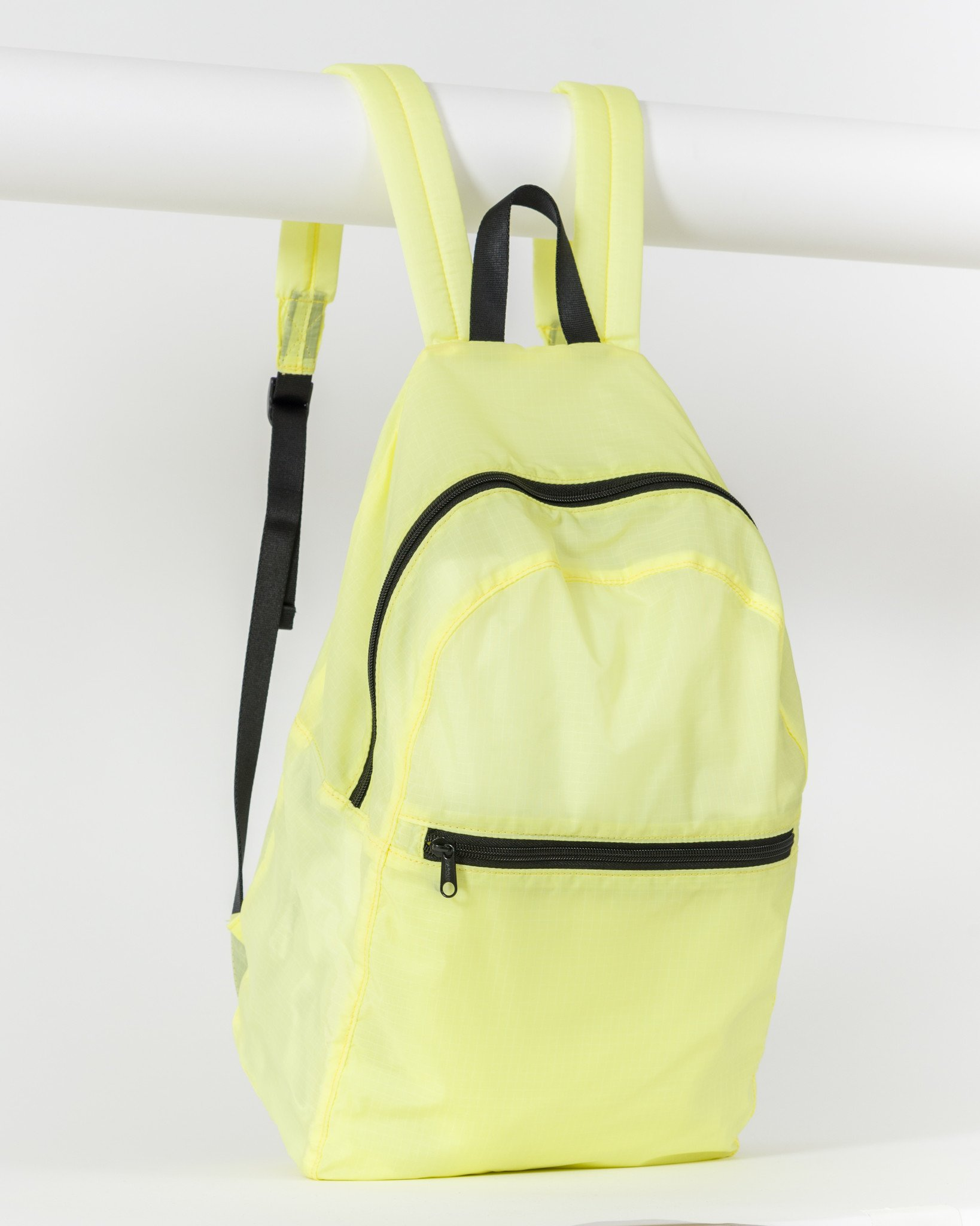 Image of a fluorescent yellow backpack that folds into a small pouch, an ideal bag for holding all the items in your zero waste travel kit