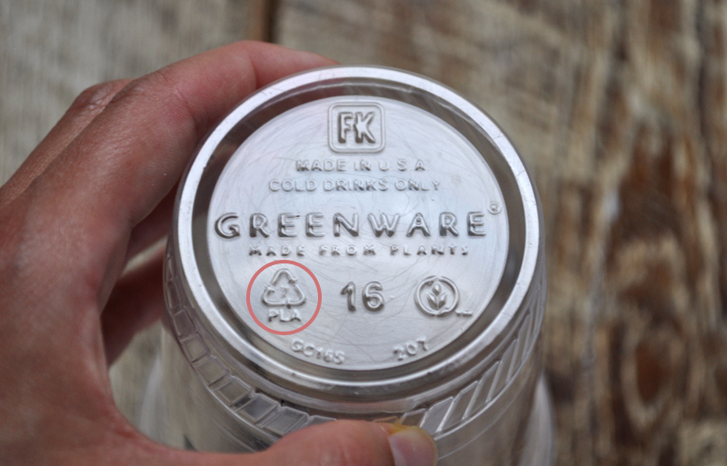 Image of a hand holding a compostable plastic cup, which is a common compostable product