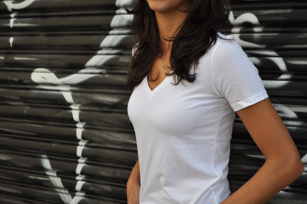 Image of a woman wearing a white v-neck t-shirt by Everlane, a sustainable fashion brand