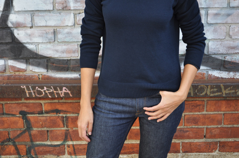 Image of a woman wearing a blue sweater and a pair of blue jeans, both part of Everlane's sustainable fashion line