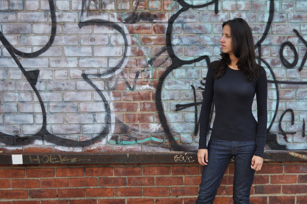 Image of a woman wearing a black long sleeve shirt and blue jeans, in front of a red brick wall with graffiti on it