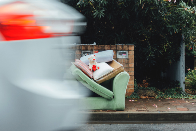 a photo of a couch on the side of the road for trash pick-up