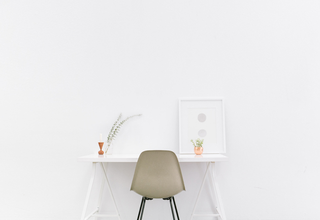 a picture of a minimally decorated white desk and chair