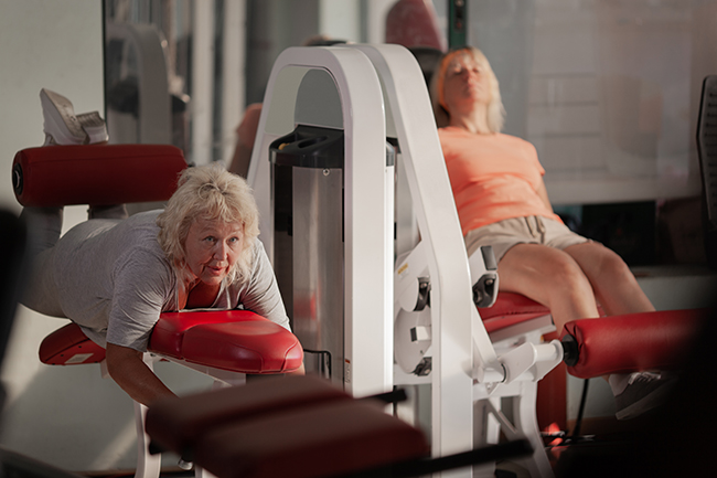 Image of Two middle aged women working out in a gym