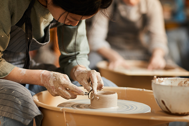 Image of a woman in apron sitting at pottery wheel and using craft tool while shaping wet clay vessel