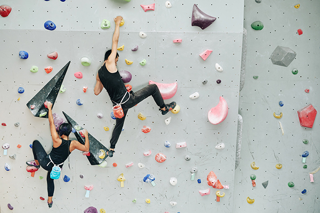 Image of a Couple practicing rock climbing on artificial wall indoors