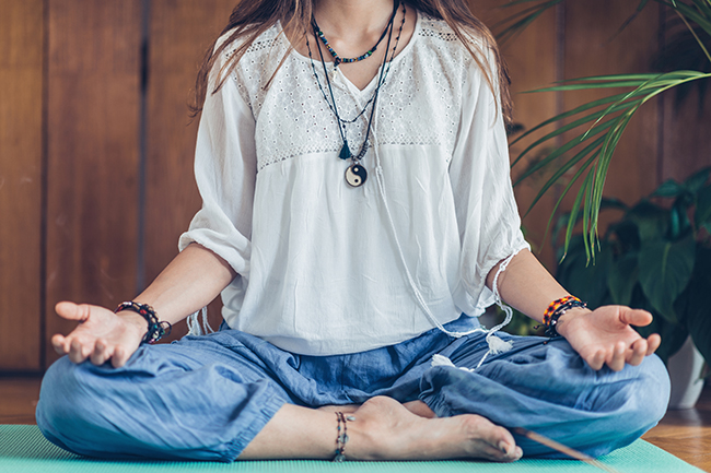 Image of a Young woman meditate while practicing Yoga. Sitting in lotus position, relaxing and enjoying incense stick after yoga class.