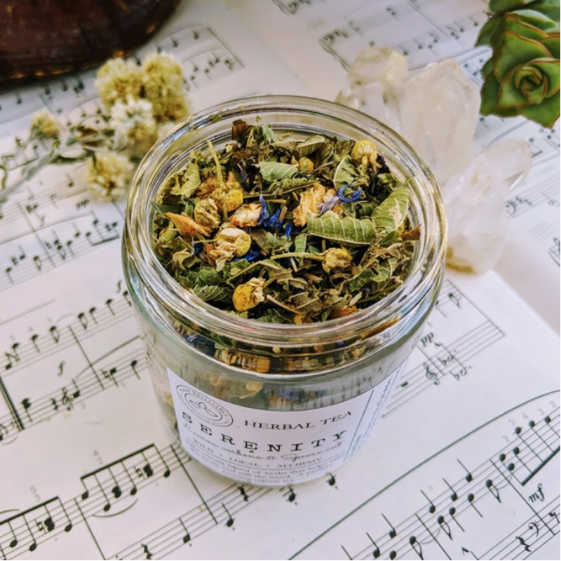 Image of a glass jar filled with herbal tea on top of sheet music