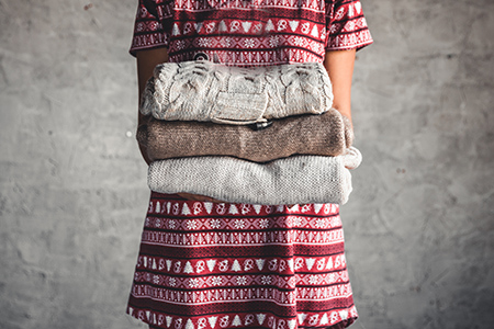 image of a woman holding a stack of sweaters