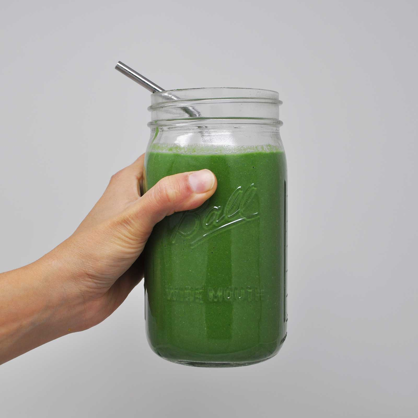 Image of a hand holding a glass jar filled with a green smoothie and a metal straw