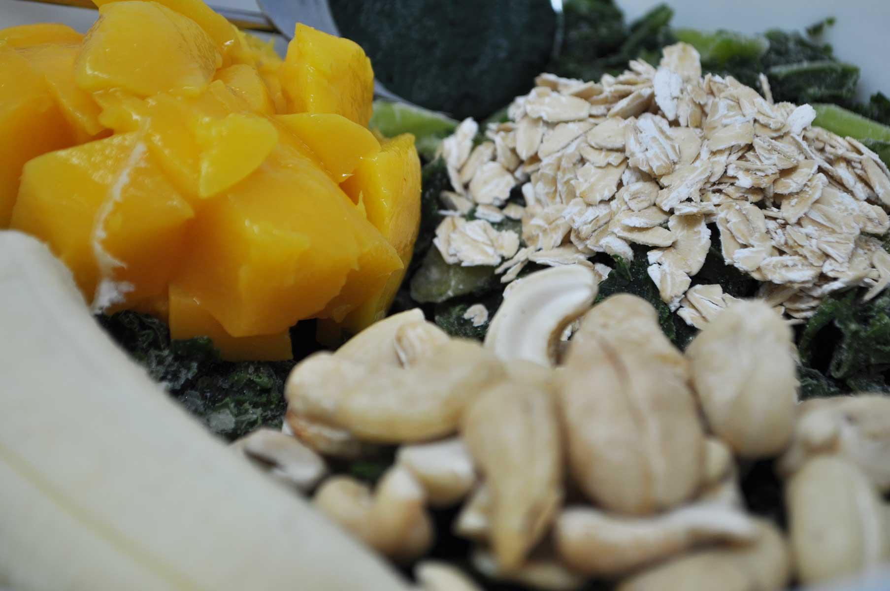 Image of chopped mango, kale, cashews, oats, and spirulina
