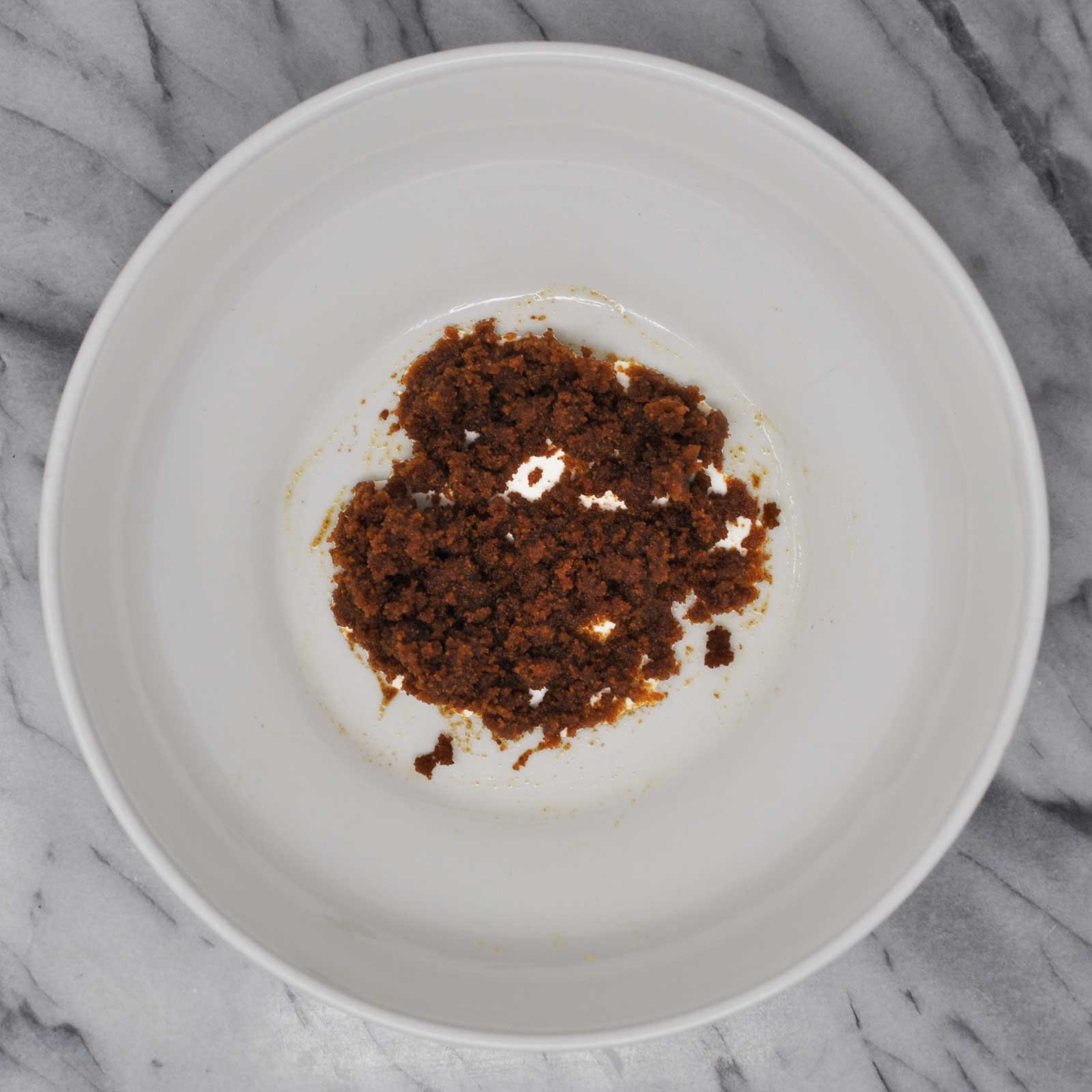Image of brown sugar mixed with olive oil in a white bowl resting on a marble countertop