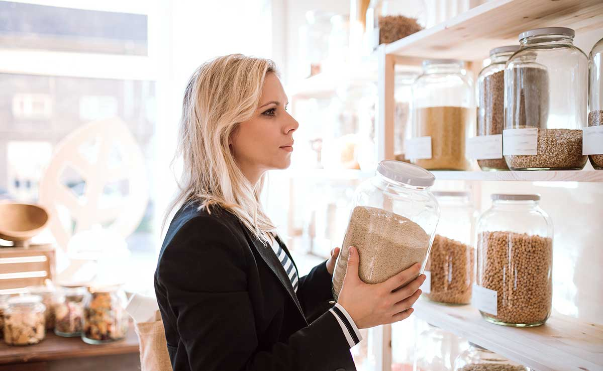 image of a woman shopping for bulk goods, something that a sustainability coach can help you with