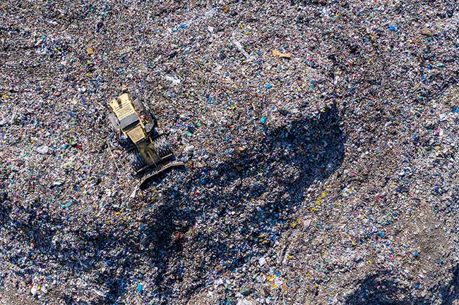 Image of a bulldozer on top of a landfill from an aerial view