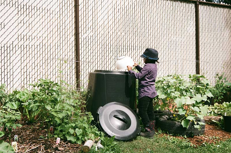 Image of a young girl putting food scraps into a compost bin