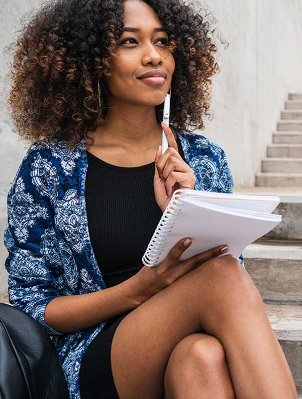 Image of a black woman sitting on a saitcase with a pen and notebook in her hands