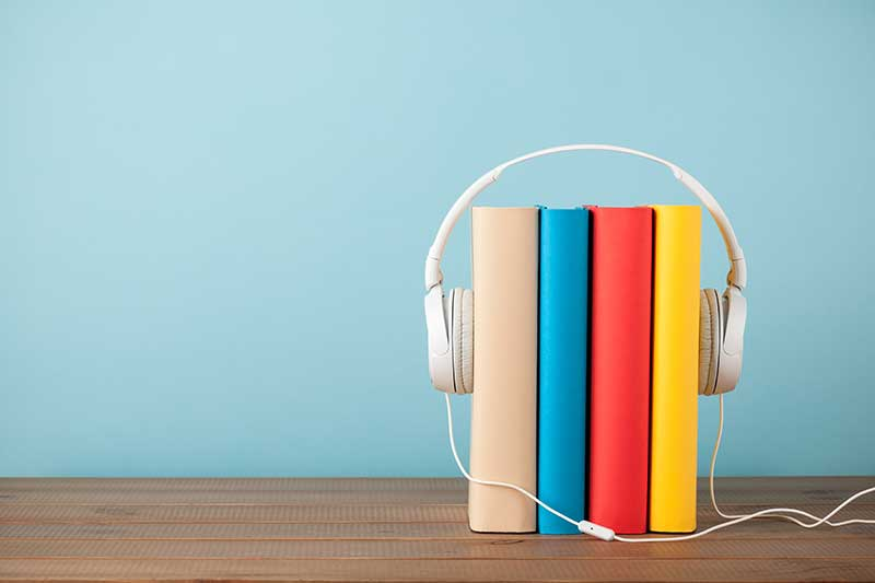 Image of a stack of books wearing headphones, audiobooks are one of the best Christmas gifts for 2020