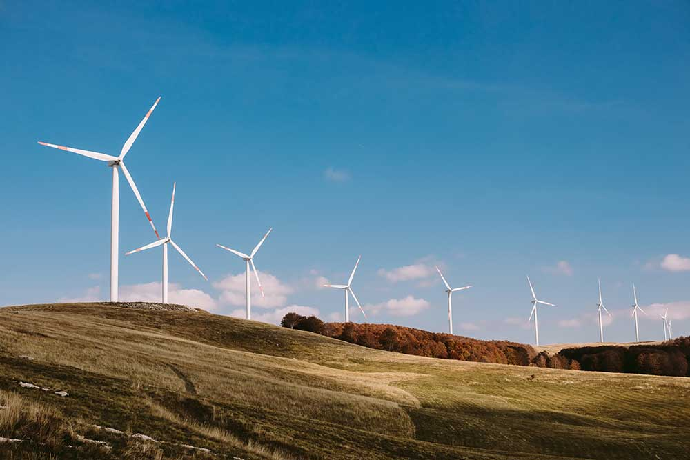 Image of windmills against a blue sky, sitting on a green hill