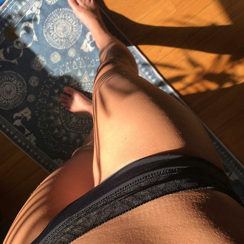 Image of a womman wearing black lace period panties standing on a blue yoga towel