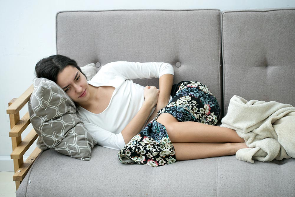 woman in stomach pain lying on a couch